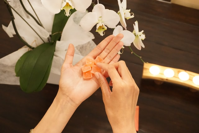 A hand taking vegan gummies from best vegan needs businesses.