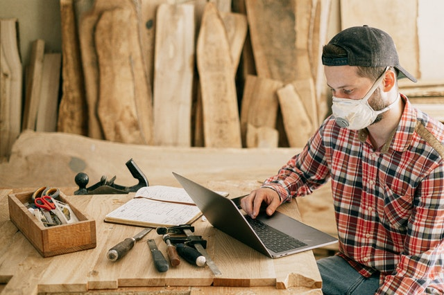 A handyman with a mask on using a laptop to find nuts and bolts supplies with tools on his table.
