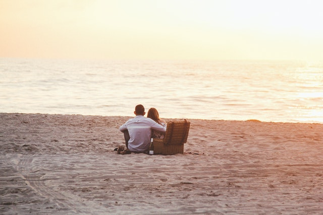 A couple on a beach on a picnic with products from an online store.