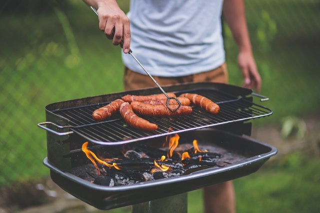 A man grilling sausages at an outdoor picnic with products bought online.