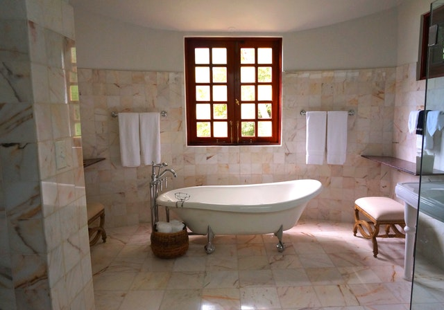 A bathroom with tiles and mosaics on the walls.