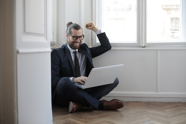 A man smiling and cheering as he stays up to date with news by reading the best business related blogs on his laptop.