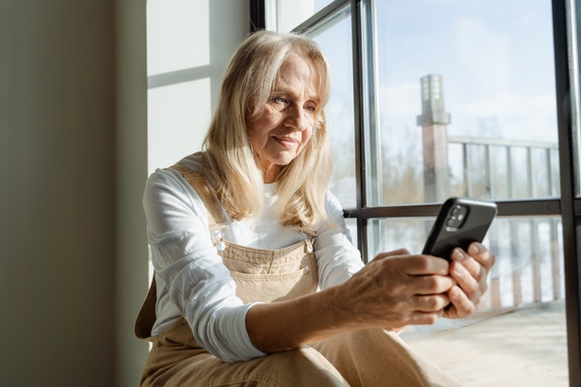 A woman at a window looking at a phone with a virtual phone system provider in the US.