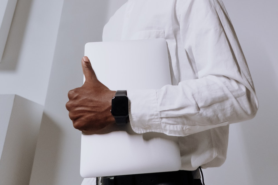 A man holding a laptop showing the Apple watch band he bought from an online store.