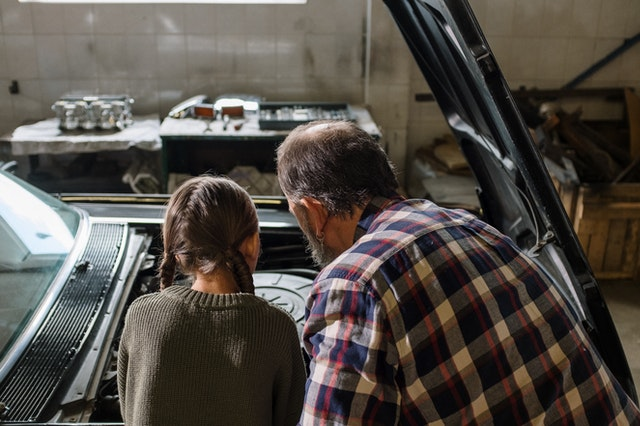 A father and daughter looking in a car to repair it at a best US autocare store.