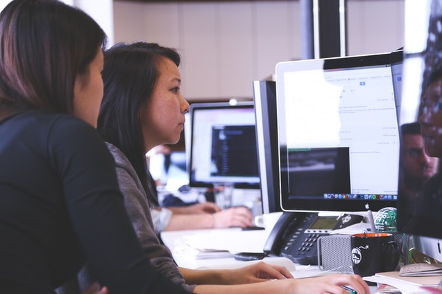 A woman looking at a computer as a corporate career coach teaches her what she needs.