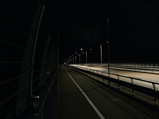 A highway at night with guardrail from a best US provider.