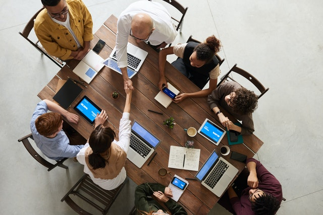 An IT consulting firm team at a table with their laptops supporting clients.