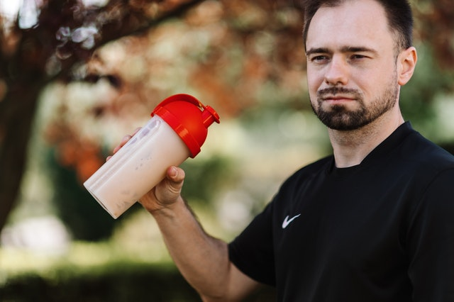 A man drinking a weight loss product from a shaker.