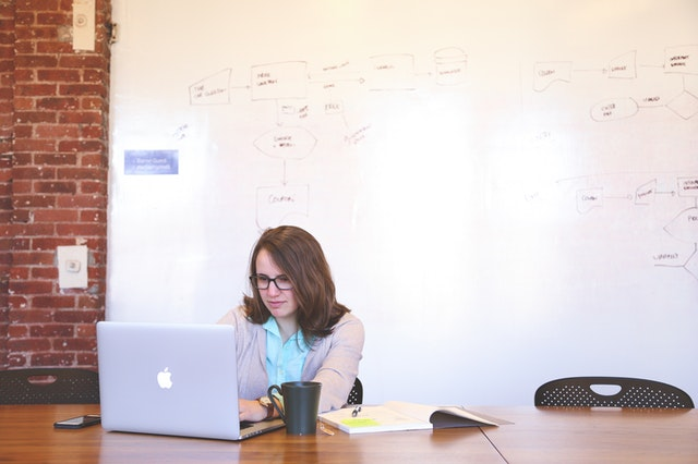 A woman on a laptop in front of a whiteboard using a free website builder online.