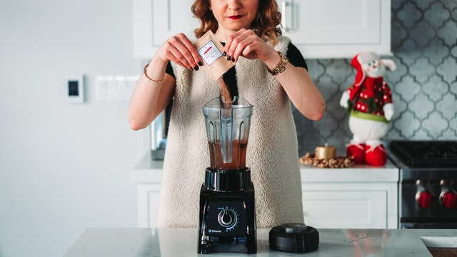 A woman pouring a best weight loss product into a blender to drink.