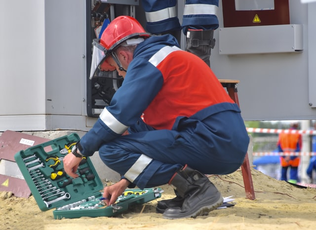 A telemetry solutions provider kneeling to get tools for a remote area installation.