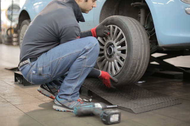 A man changing a tire at a US vehicle repair and autocare store.