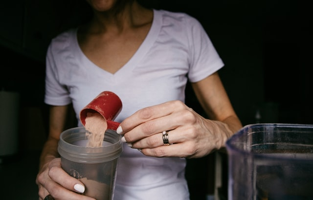 A woman using a best weight loss product to mix into a drink.
