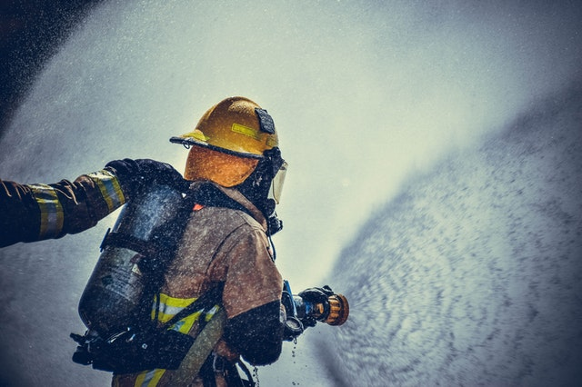 A fire fighter from a Tampa Florida fire watch service putting out a fire with a hose.
