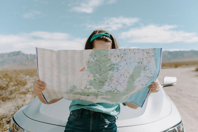 A woman sitting on a car looking at a map for her travel and lifestyle blog.