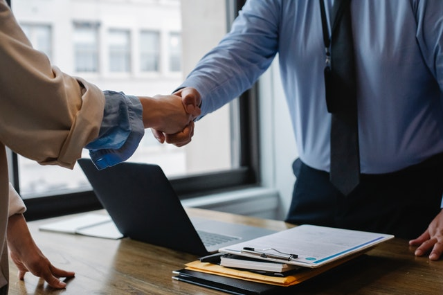 A person getting hired and shaking hands with their employer after using a career coaching company for their corporate needs.