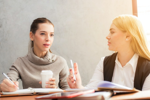 Two women from a career coaching company with coffee discussing their corporate needs.