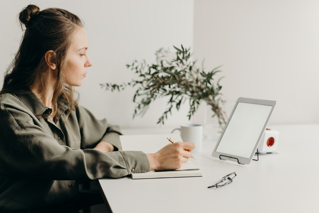 A woman using a tablet to do corporate career coaching with a top company.