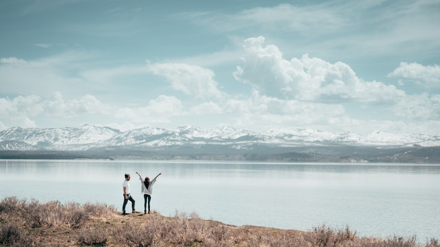 Two people with their arms raised at a lake they have travelled to for their lifestyle and travel blog.