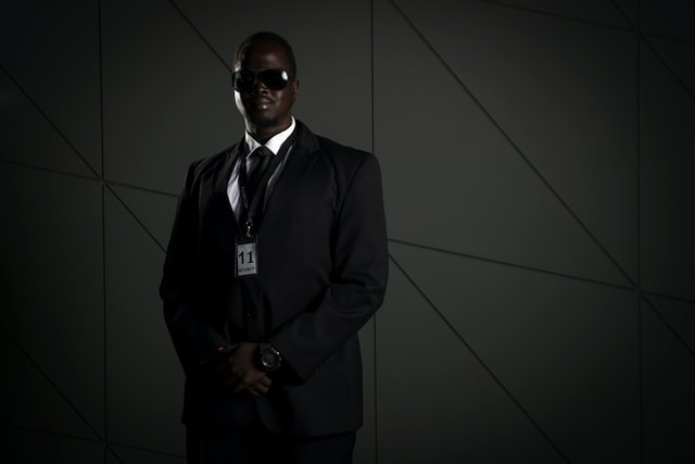 A bodyguard from Houston Texas in sunglasses and a suit.
