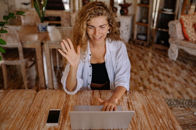 A woman waving at her laptop and learning Spanish with online classes.