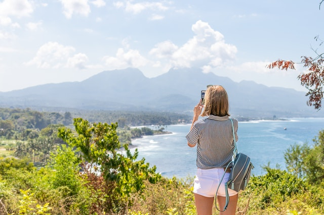 A blogger taking a photo of a beach for her lifestyle and travel blog.