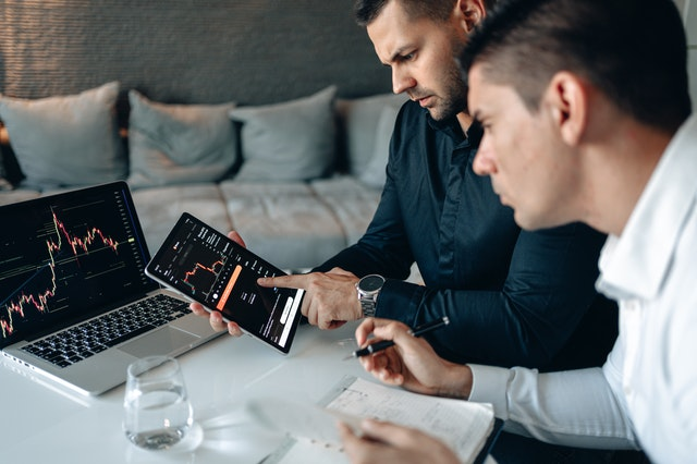 Two men from a best local SEO consulting firm in the US looking at results on a laptop and iPad.