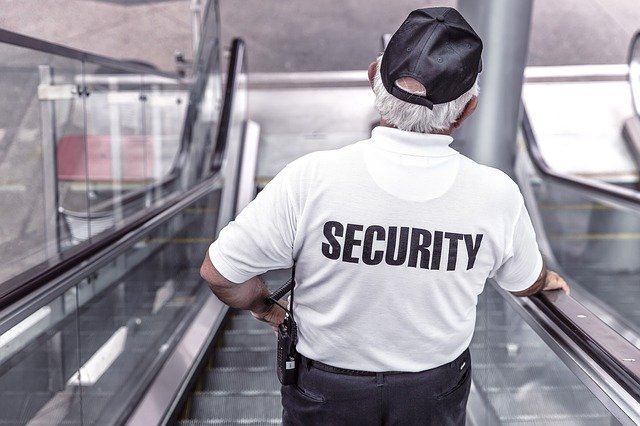 An NY security guard going down an escalator.