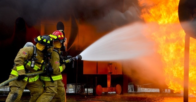 Firefighters from a Tampa fire watch service putting out a fire with their hose.