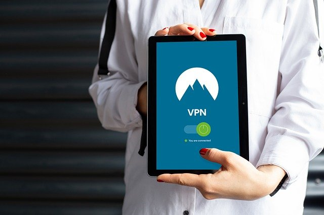 A woman holding an iPad that is protected by a US VPN.